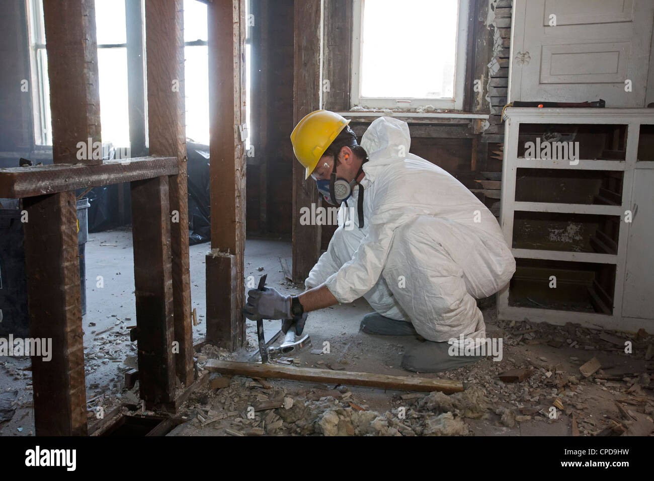 Workers salvage building materials from a home being 'deconstructed.' - Stock Image