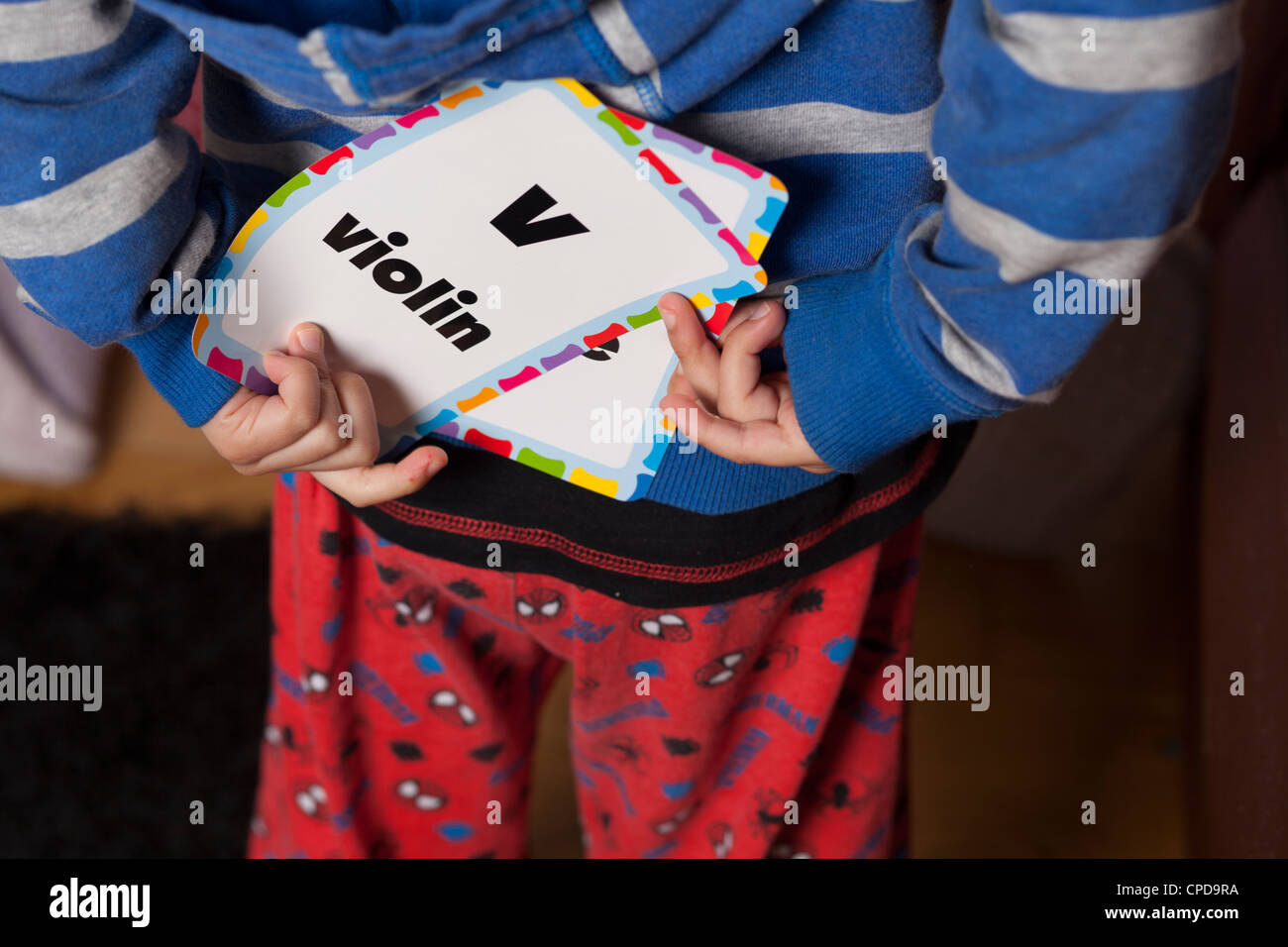 Child hides alphabet card behind his back - Stock Image
