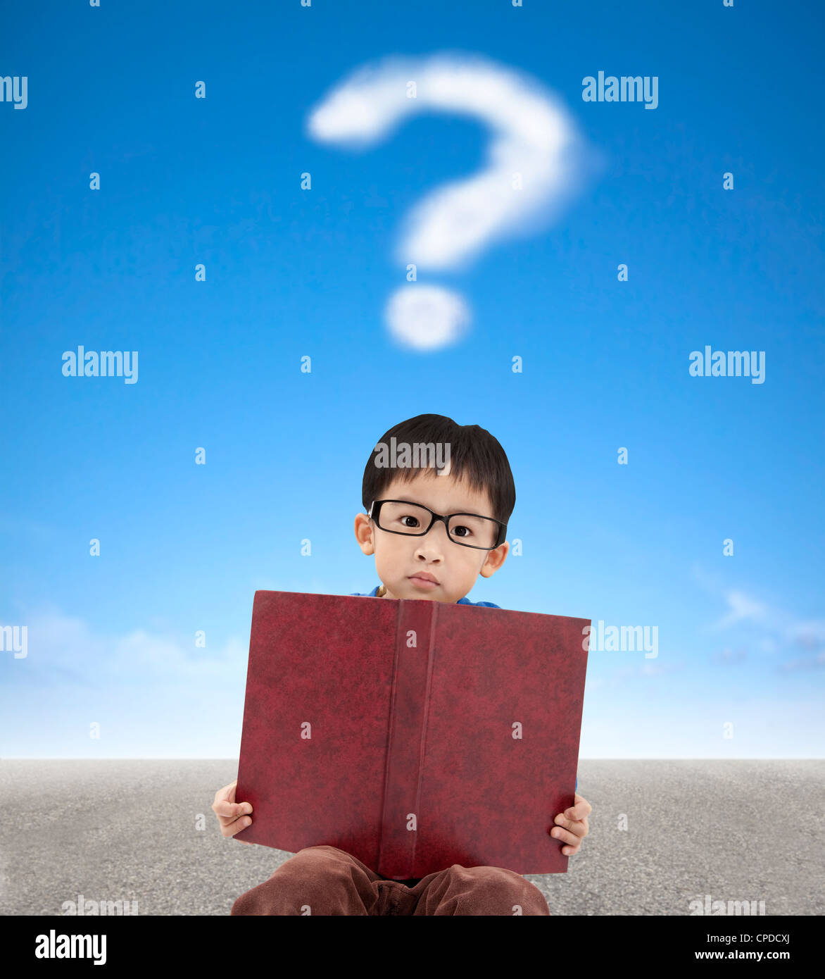 little boy holding book and question mark cloud background - Stock Image