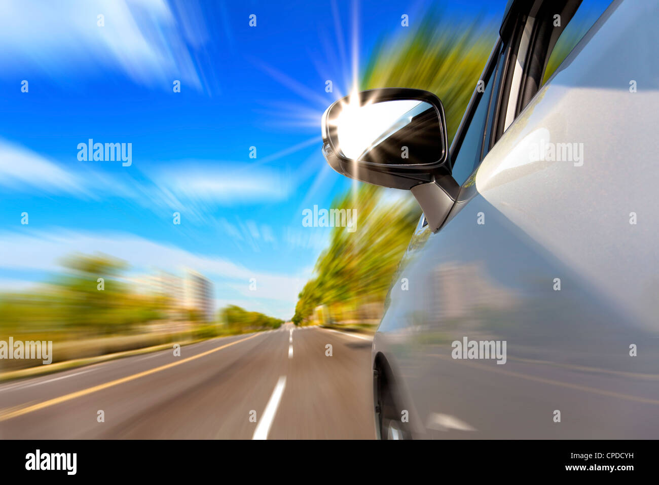 car on the road with motion blur and sunlight in the mirror - Stock Image