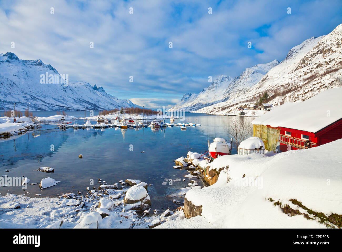 Snow covered mountains, boathouse and moorings in Norwegian fjord village of Ersfjord, Kvaloya island, Troms, Norway - Stock Image