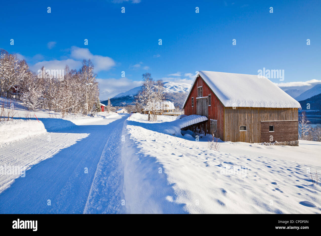 Snow covered road, barn and chalets in Norwegian village of Laukslett, Troms, North Norway, Scandinavia, Europe - Stock Image