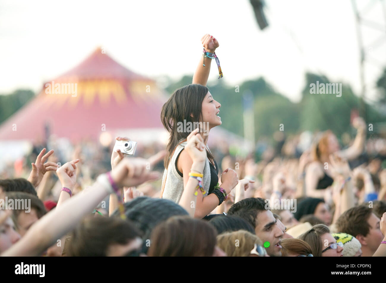 Girl at a music festival on shoulders in the crowd cheering - Stock Image