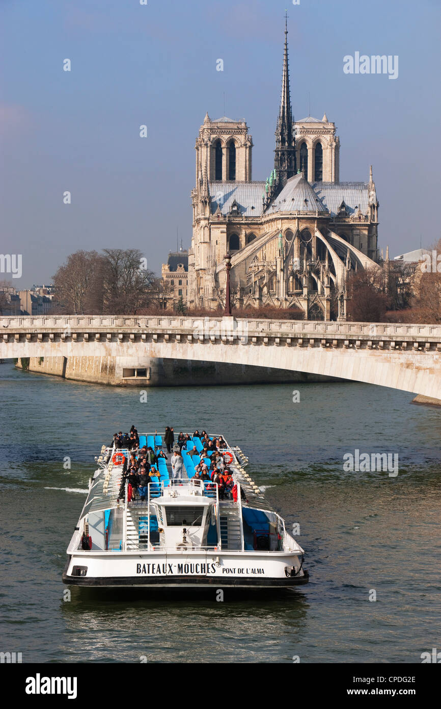 Tourist boat going under bridge on the River Seine, with Notre Dame Cathedral in background, Paris, France, Europe - Stock Image