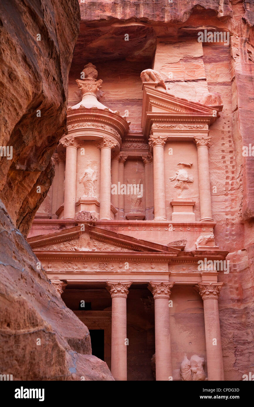 The facade of the Treasury (Al Khazneh) carved into the red rock with the Siq in the foreground, Petra, Jordan, - Stock Image