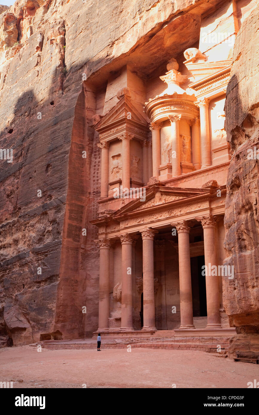 Tourist looking up at the facade of the Treasury (Al Khazneh) carved into the red rock at Petra, Jordan, Middle - Stock Image