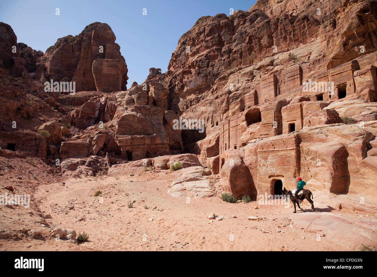 Child riding a donkey in front of cave dwellings in Petra, UNESCO World Heritage Site, Jordan, Middle East - Stock Image