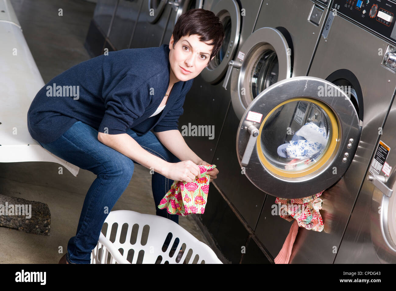 A woman toils at the laundromat - Stock Image
