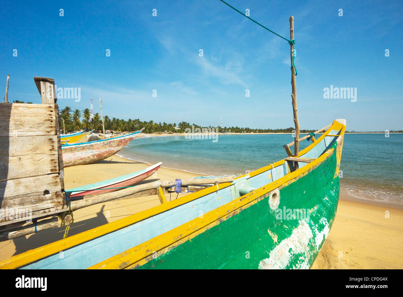 Outrigger fishing boats on this popular surf beach, badly hit by the 2004 tsunami, Arugam Bay, Eastern Province, - Stock Image