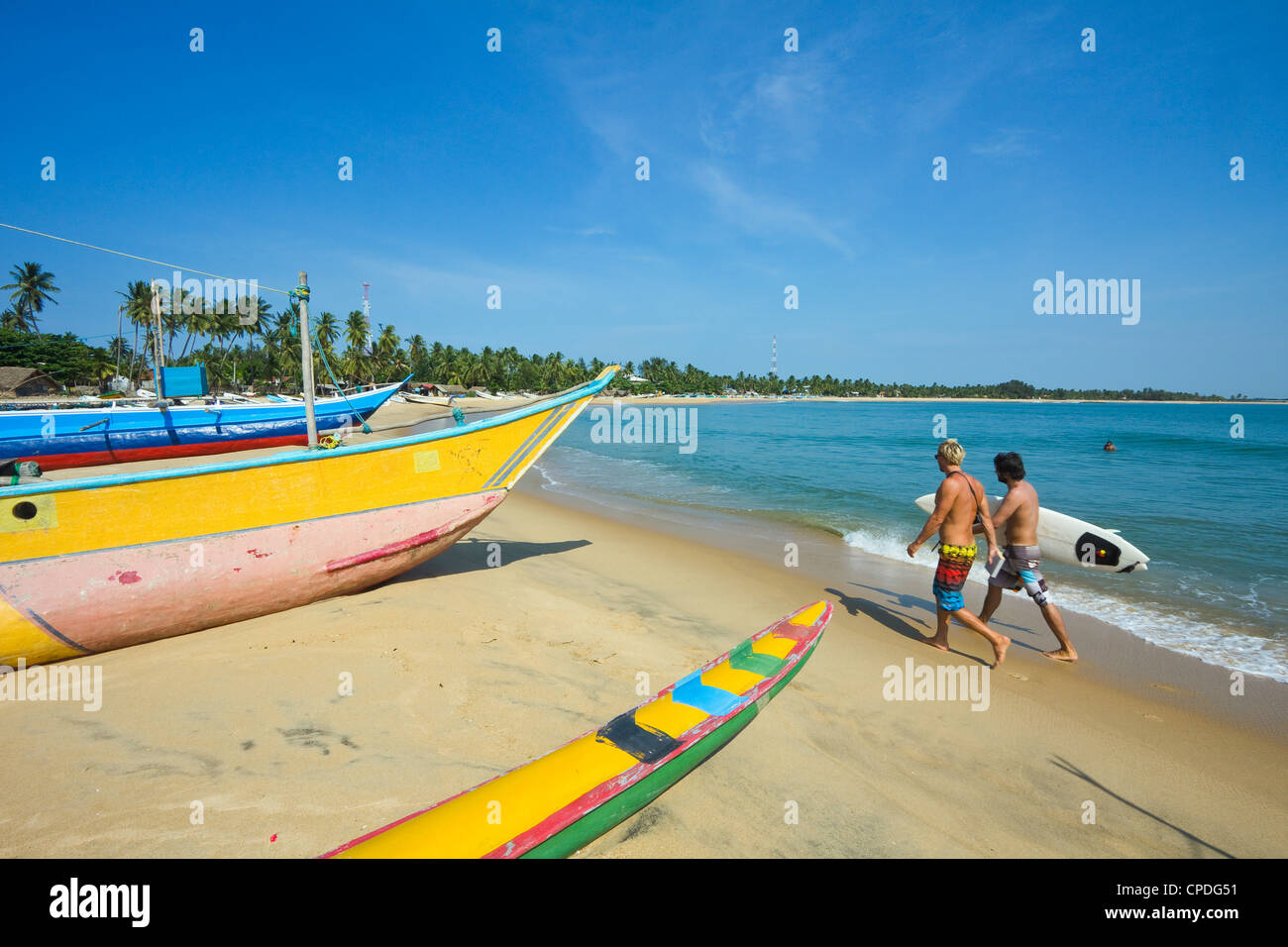 Surfers and fishing boats on this popular surf beach, badly hit by the 2004 tsunami, Arugam Bay, Eastern Province, - Stock Image
