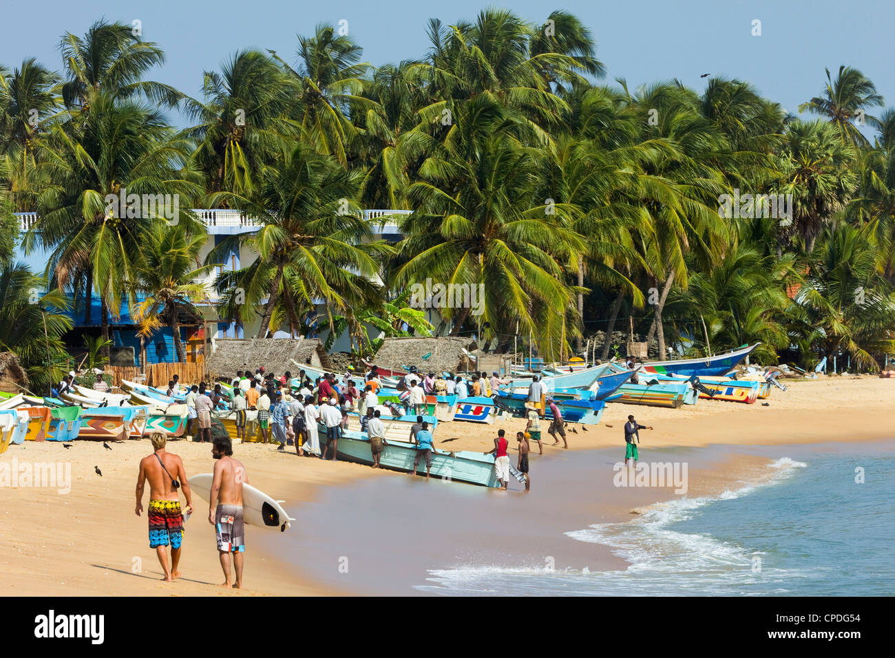 Tourists stroll whilst local fishermen work on this popular surf beach, Arugam Bay, Eastern Province, Sri Lanka, - Stock Image
