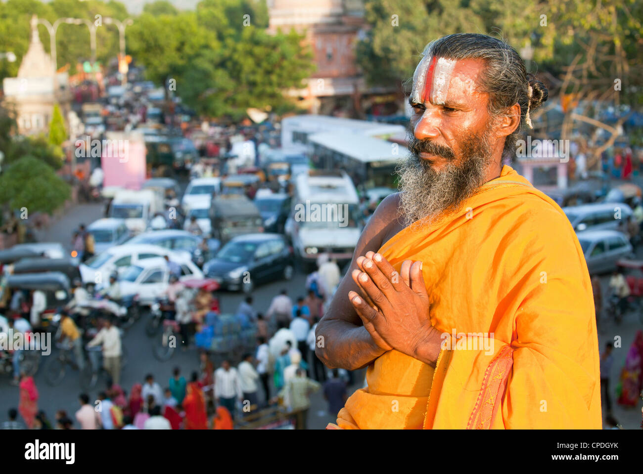 Holy Sadhu meditating high above traffic congestion and street life in the city of Jaipur, Rajasthan, India, Asia Stock Photo