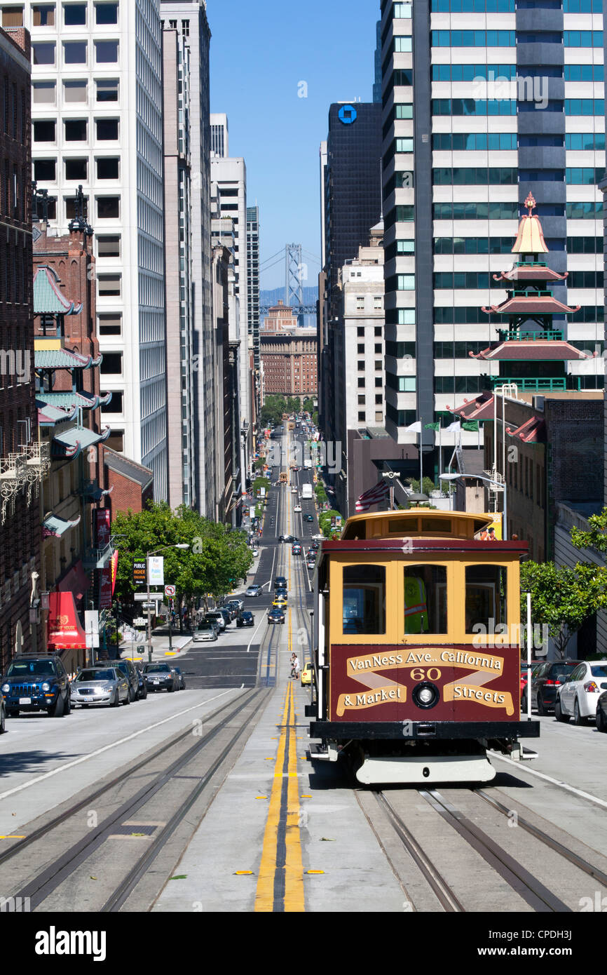 Cable car crossing California Street with Bay Bridge backdrop in San Francisco, California, USA - Stock Image