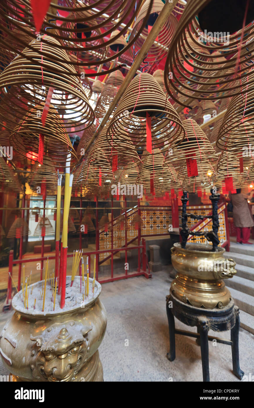 Incense coils hang from the roof of the Man Mo Temple, built in 1847, Sheung Wan, Hong Kong, China, Asia - Stock Image