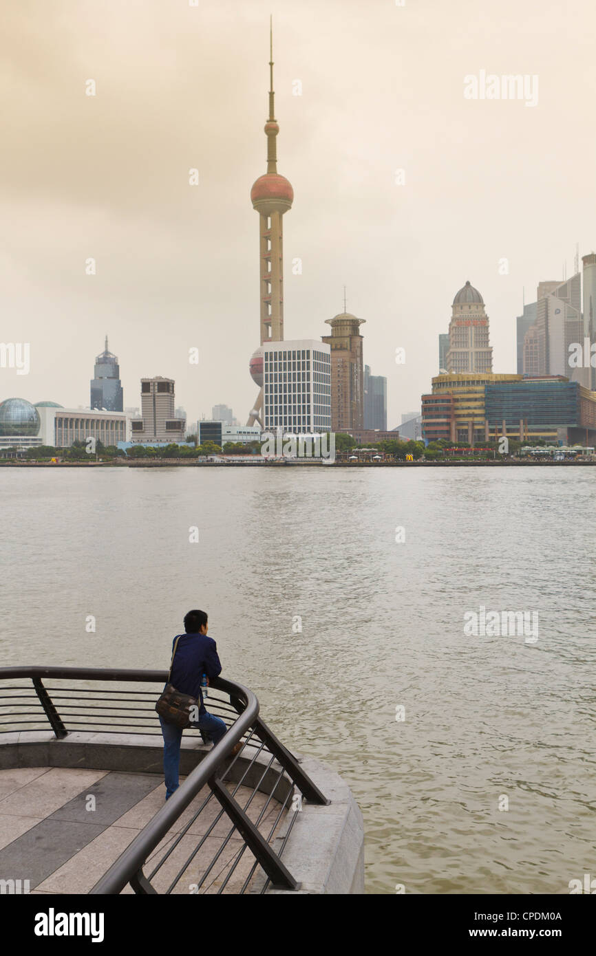 A man looking at the Oriental Pearl Tower and Pudong skyline across the Huangpu River from the Bund, Shanghai, China, - Stock Image