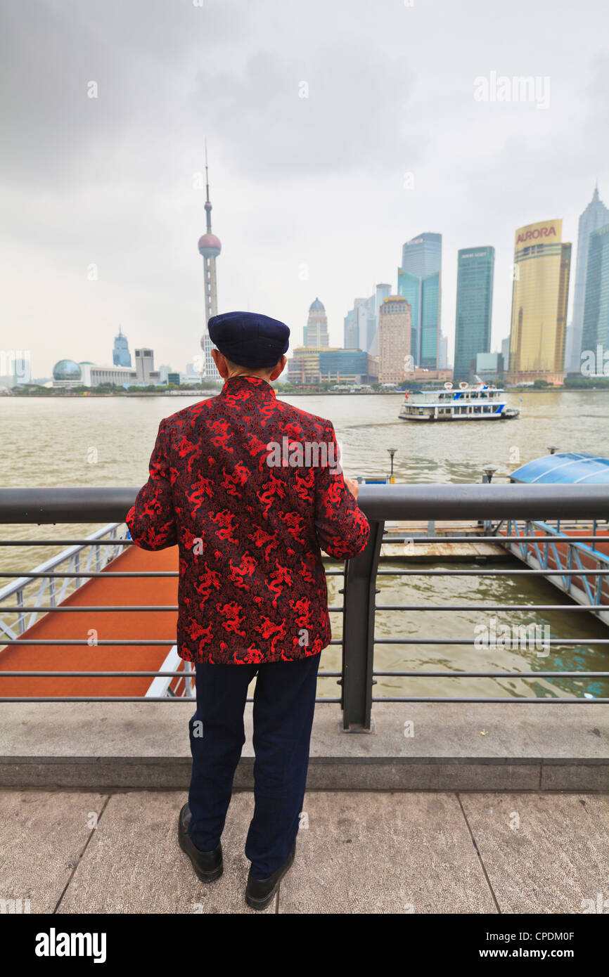 A man looking at the Pudong skyline from the Bund across the Huangpu River, Shanghai, China, Asia - Stock Image