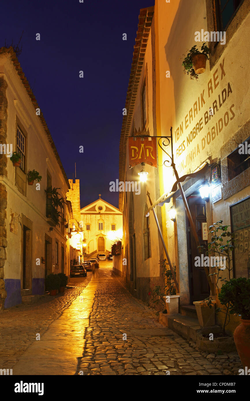 Rua Direita at night, the cobbled street that runs through the mediaval walled city of Obidos, Estremadura, Portugal, - Stock Image
