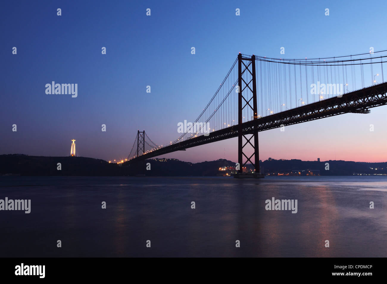 The 25 April Suspension Bridge at dusk over the River Tagus (Rio Tejo), Christus Rei is illuminated at Almada, Lisbon, - Stock Image