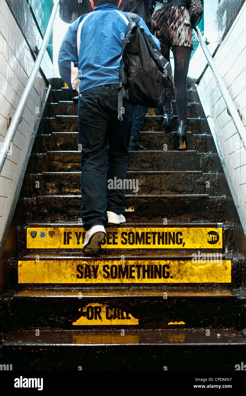 People leaving New York City subway station in rain with 'if you see something say something' warning on - Stock Image