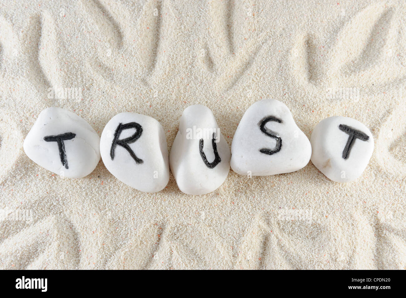 Trust word on group of stones on the sand - Stock Image