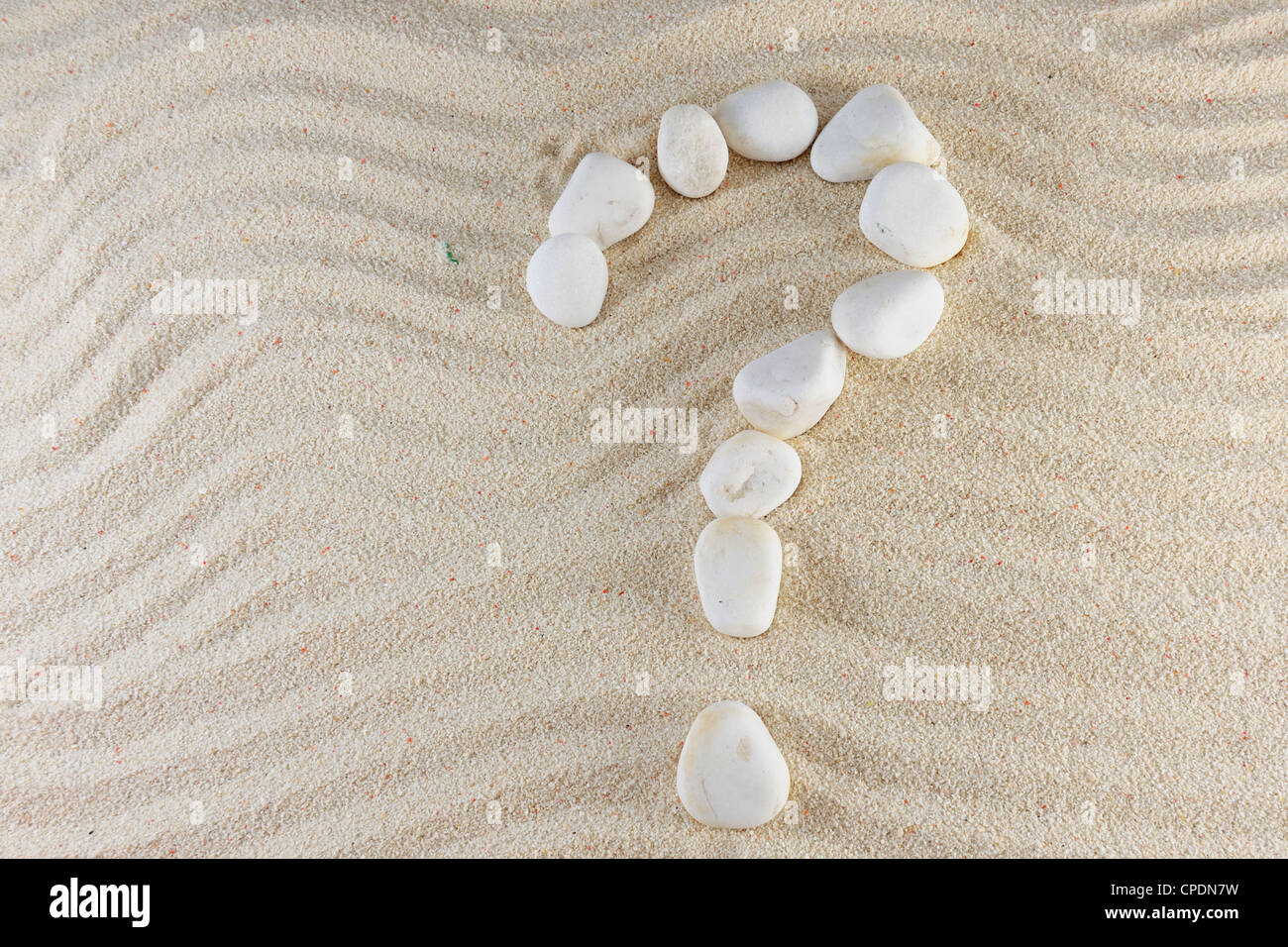 Question mark made of stones with sand as background - Stock Image