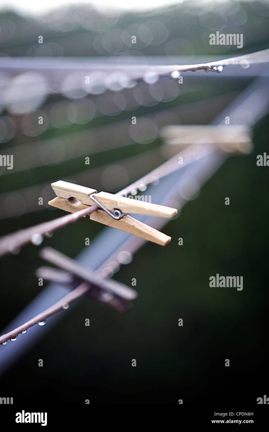 Wooden clothes pegs on wet washing line - Stock Image
