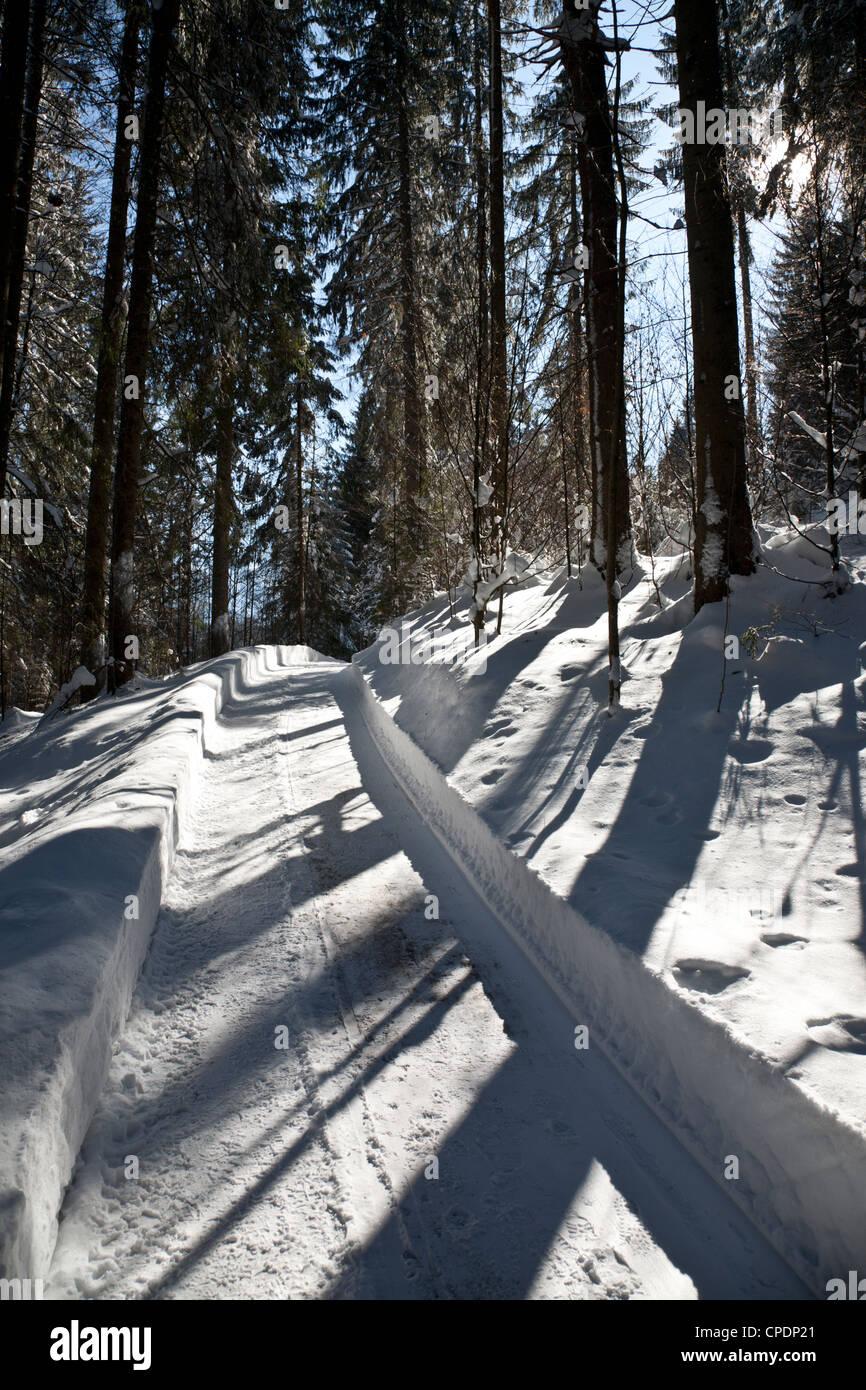 Deep, crisp snow on an alpine footpath through woods at Garmisch-Partenkirchen, Germany - Stock Image