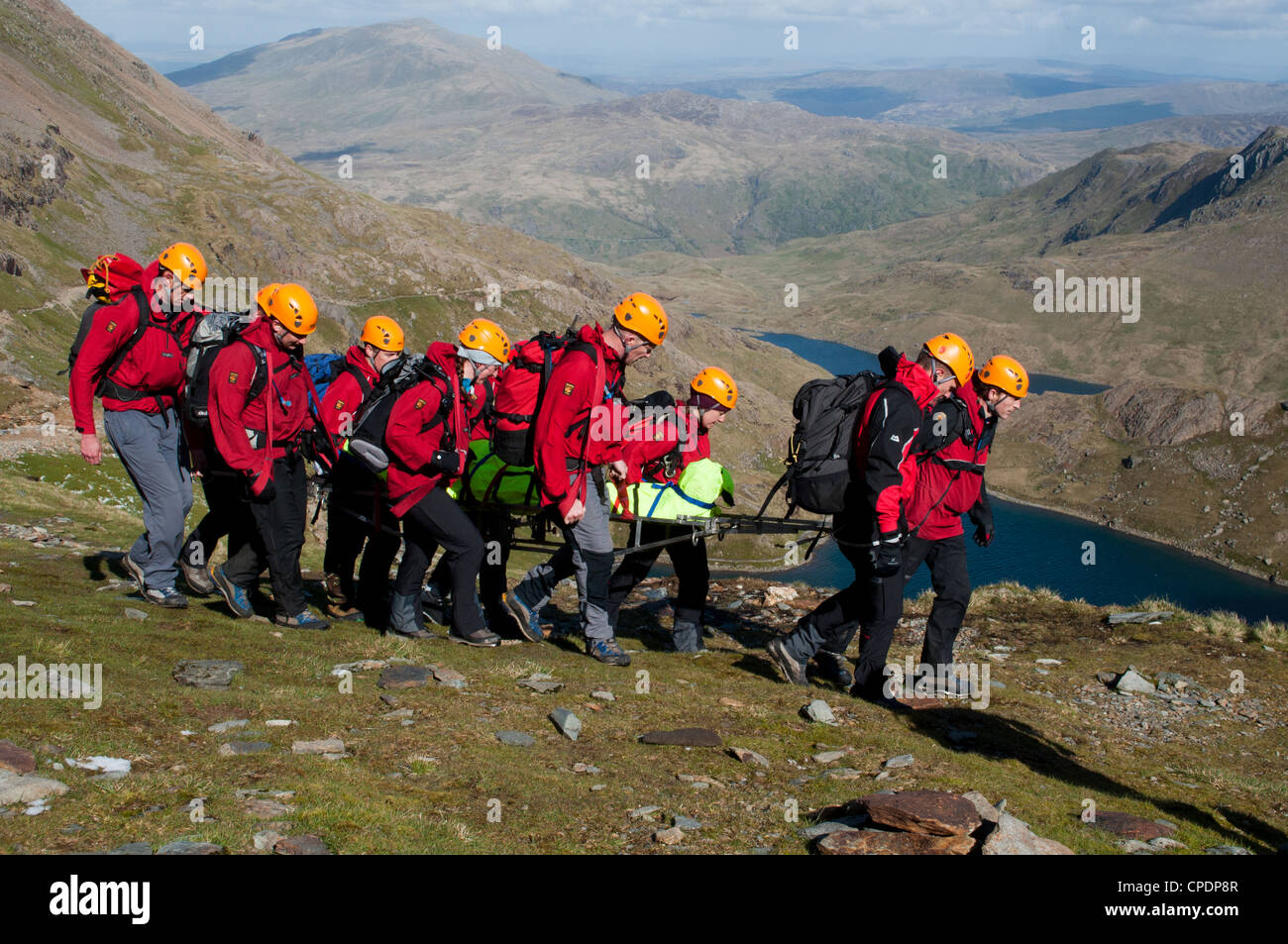 Mountain Rescue team members move stretcher with casualty to await rescue helicopter, Miners Track Snowdon - Stock Image