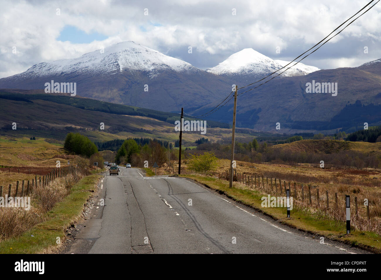 a82 trunk road through the scottish highlands with snow covered mountains ben more left and stobinian near tyndrum - Stock Image