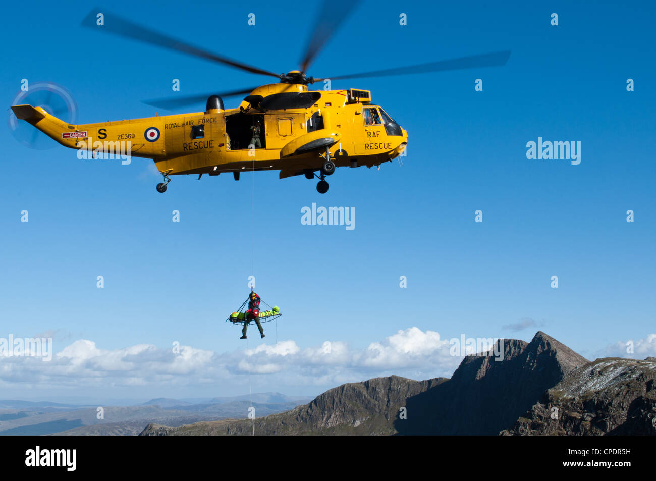 Sea King Helicopter from RAF Valley, assisted by Mountain Rescue Teams rescuing injured walker in Snowdonia - Stock Image