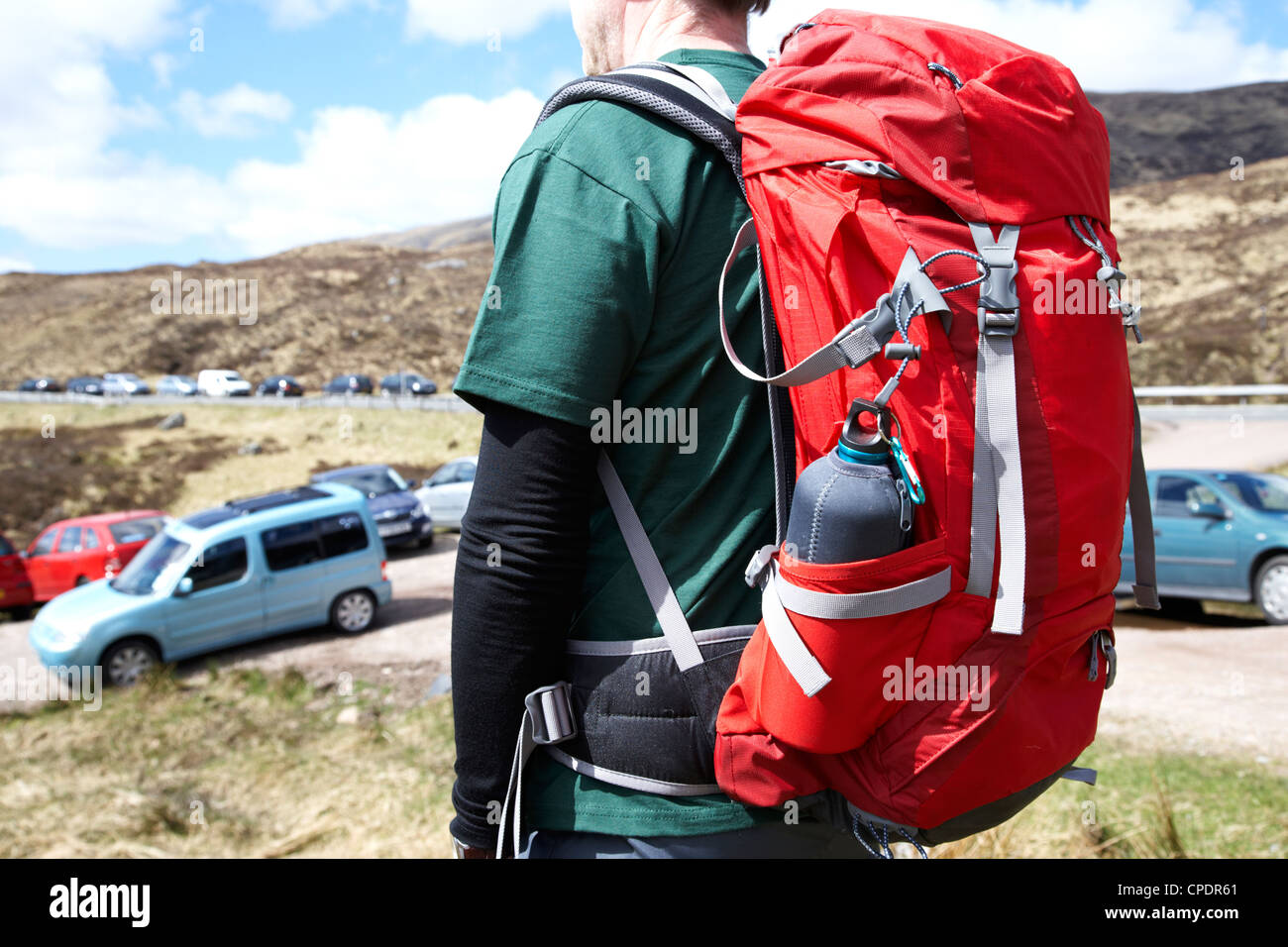 hiker hillwalker leaving busy side road with lots of cars parked in the highlands of Scotland UK - Stock Image