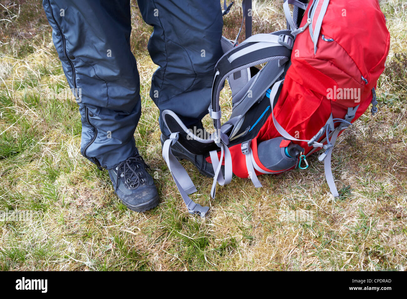 hiker hillwalker wearing boots waterproofs and rucksack in the highlands of Scotland UK - Stock Image