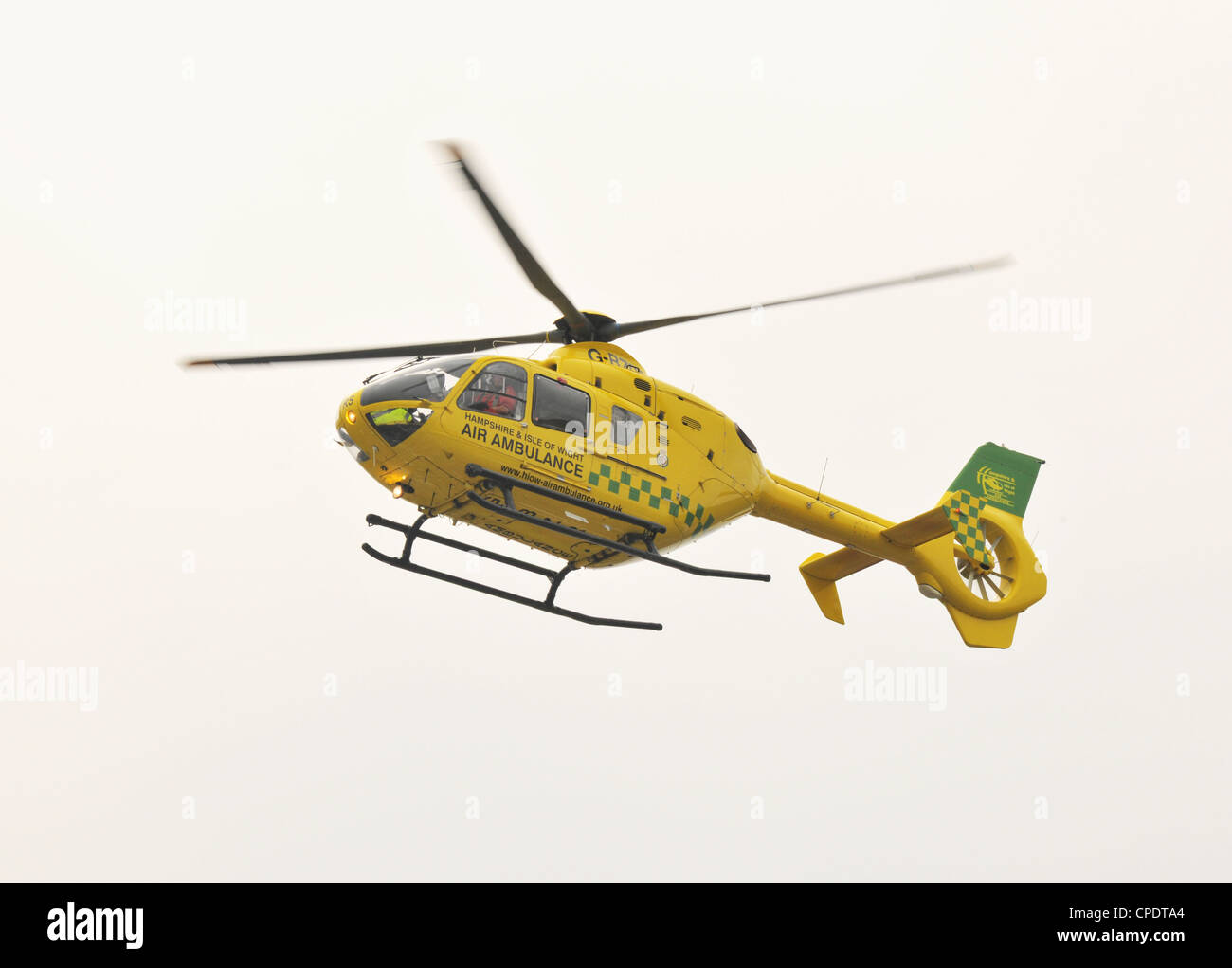 Hampshire May 2012. Hampshire and Isle of Wight Air Ambulance in flight on a dull day. - Stock Image