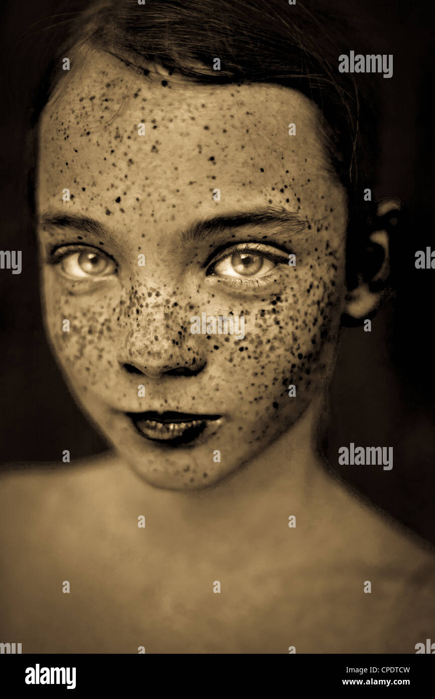 A close up of a young girl's face in sepia tones. - Stock Image
