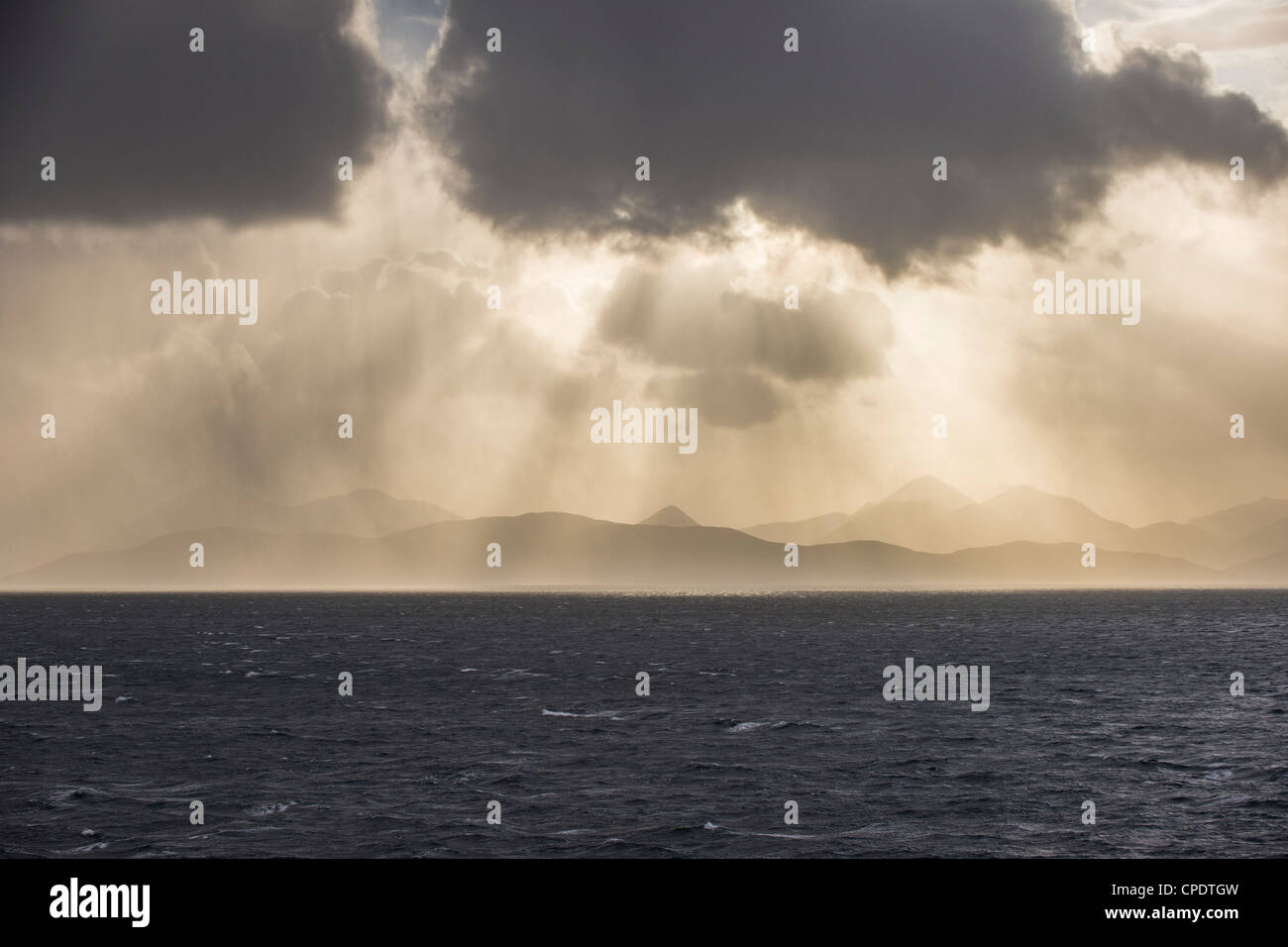 Dramatic storm clouds and shafts of sun light over The Cuillin on the Isle of Skye from Applecross, Highlands, Scotland, - Stock Image