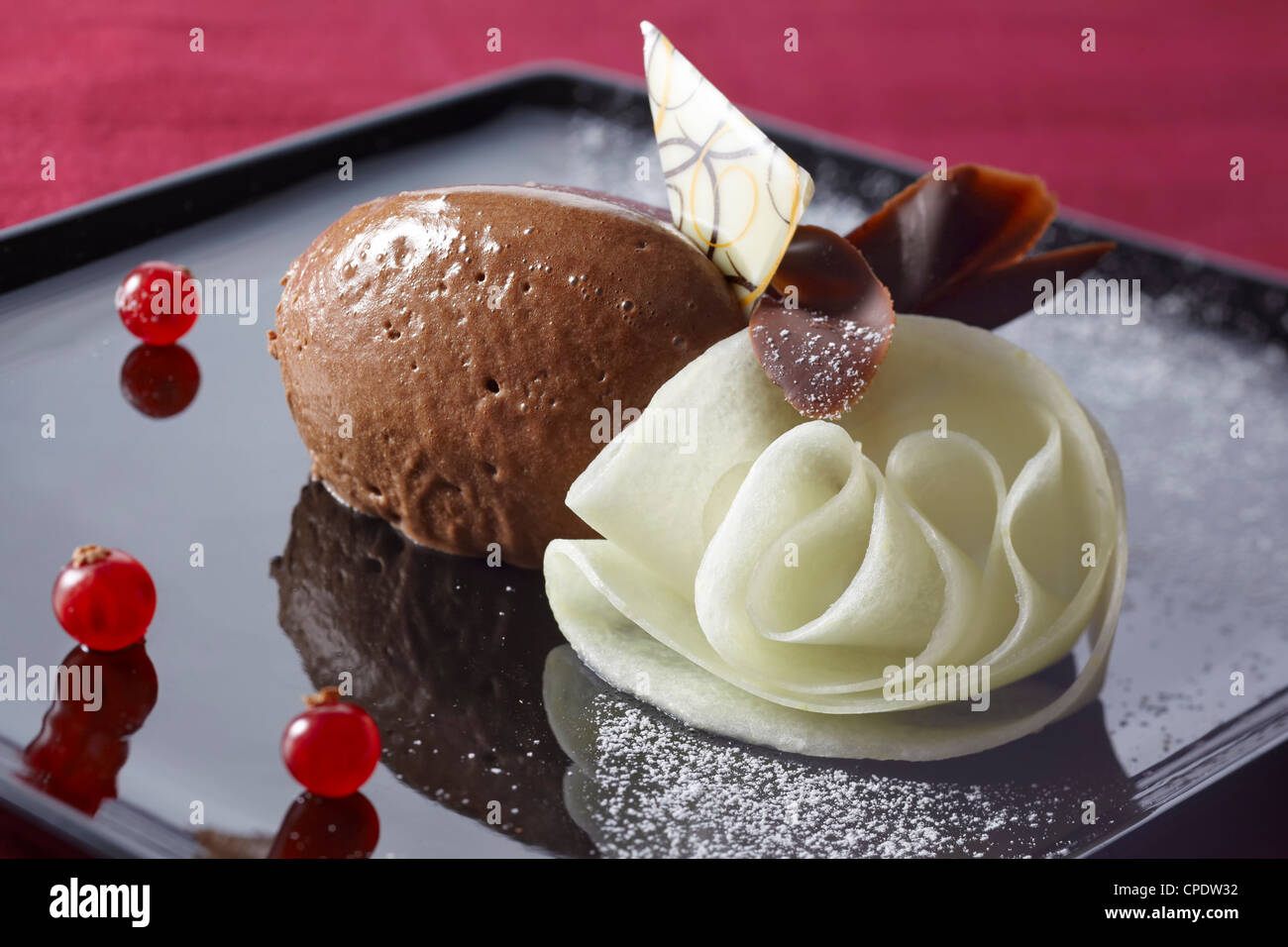 Mousse au chocolate and a blossom formed from melon, decorated with currants and chocolate chips. Red table cloth. - Stock Image