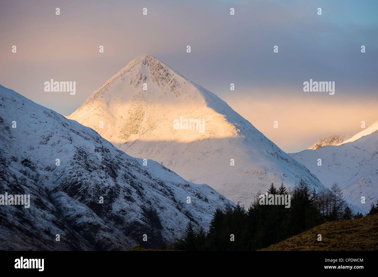 Shaft of golden sunlight on a snowy covered mountain, Glen Sheil, Highlands, Scotland, UK Stock Photo