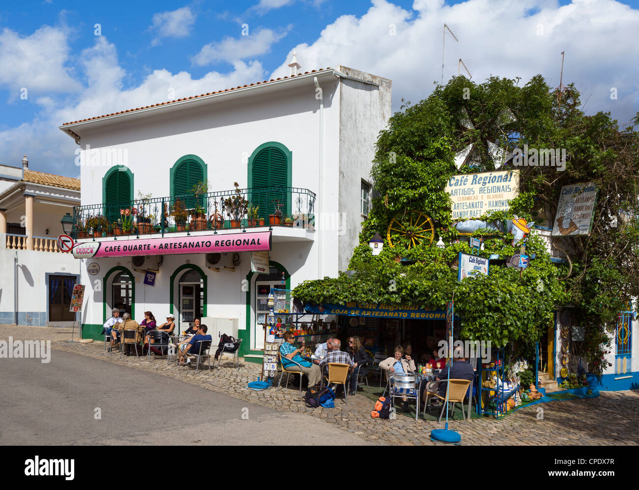 Cafe in the centre of the inland village of Alte with the village church to the left, Algarve, Portugal - Stock Image