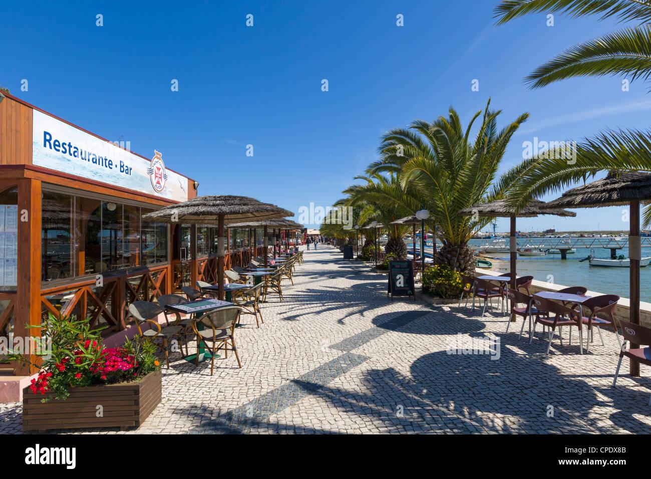Seafront restaurants by the harbour in the resort of Alvor, near Portimao, Algarve, Portugal Stock Photo
