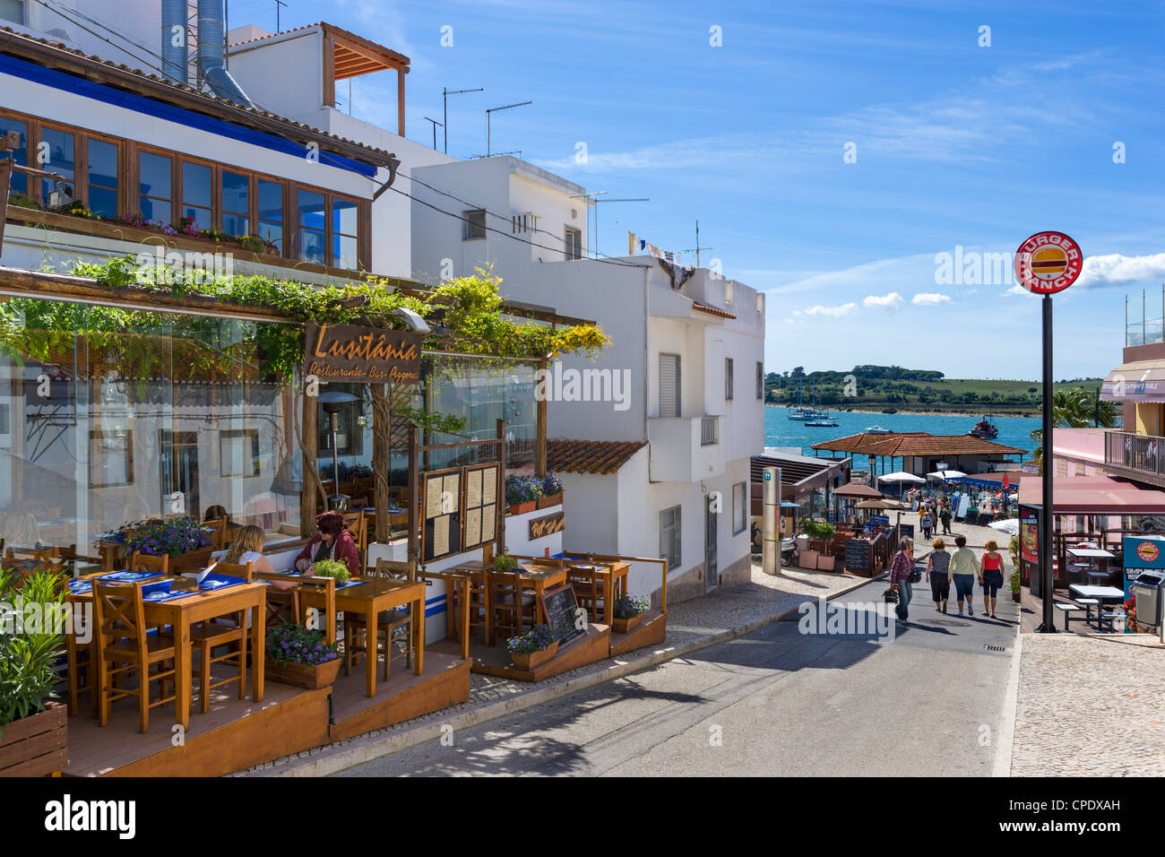 Shops and bars in the centre of the resort of Alvor looking towards the harbour, near Portimao, Algarve, Portugal - Stock Image