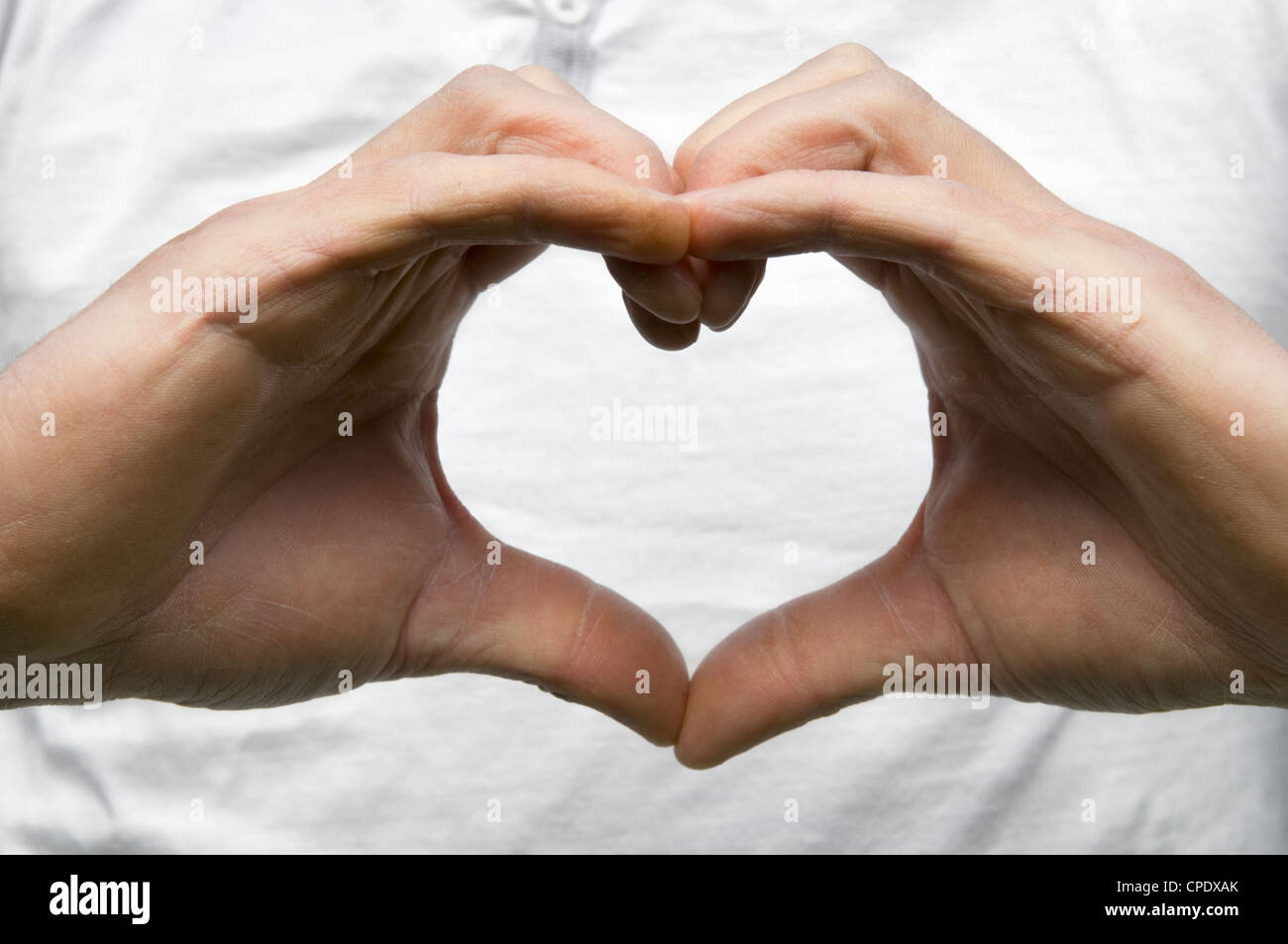 Caucasian male hands forming heart shape against white t-shirt showing concept of either love or look after your - Stock Image
