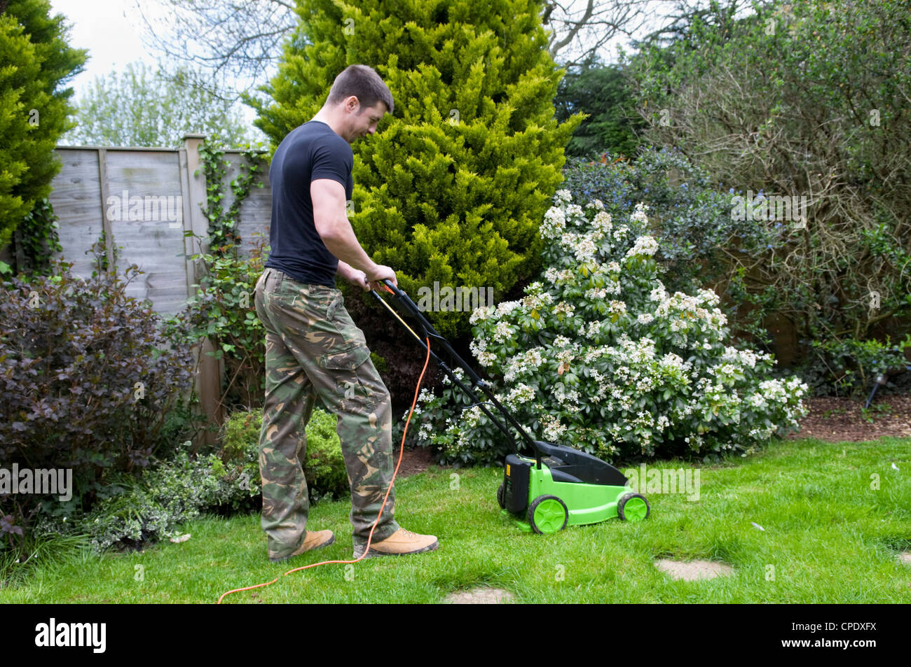 Caucasian man mowing lawn in garden in Bristol, UK - Stock Image