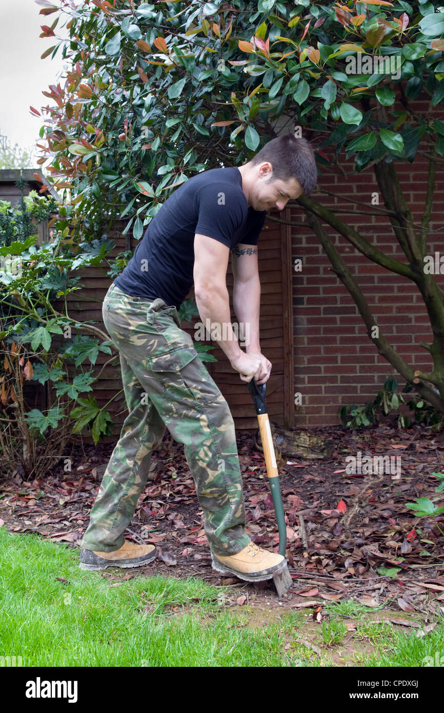 Caucasian man digging out border with garden spade in garden in Bristol, UK - Stock Image