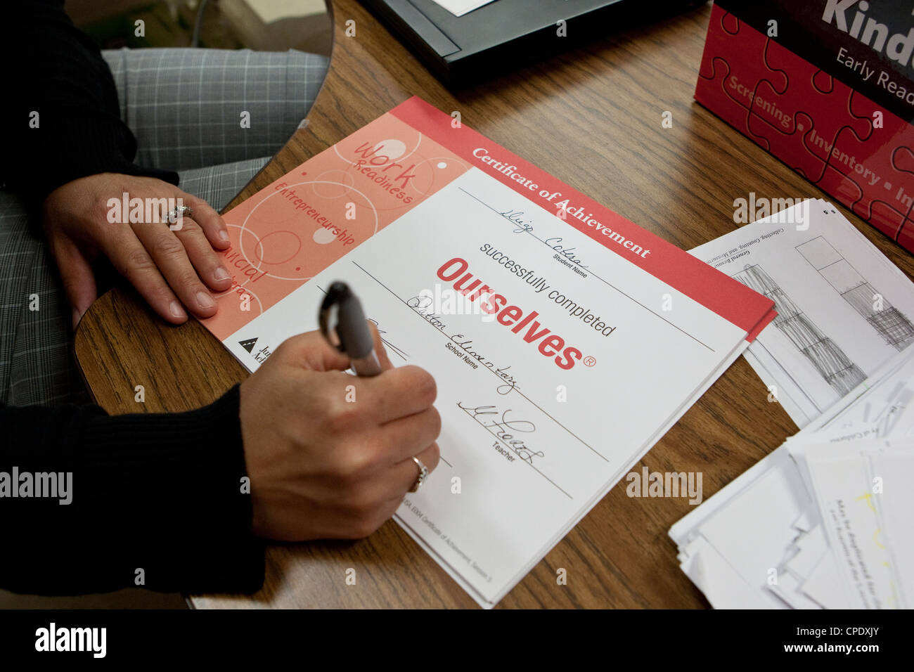 Kindergarten teacher fills out a certificate of achievement for students of Texas public elementary school - Stock Image