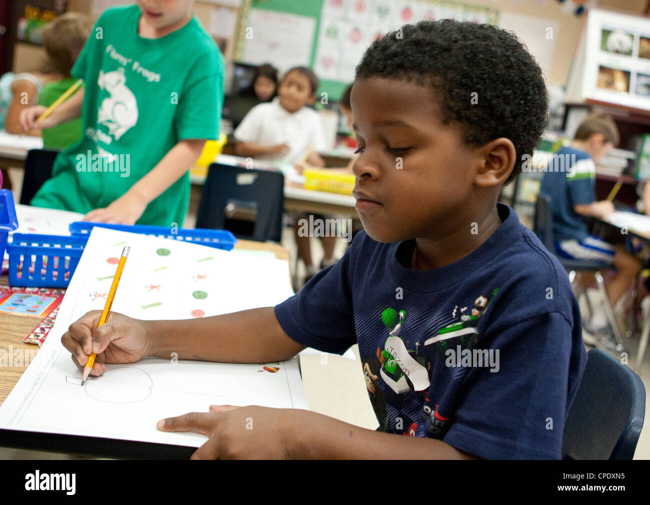 African-American male kindergarten student works at his desk during class at Texas public elementary school - Stock Image