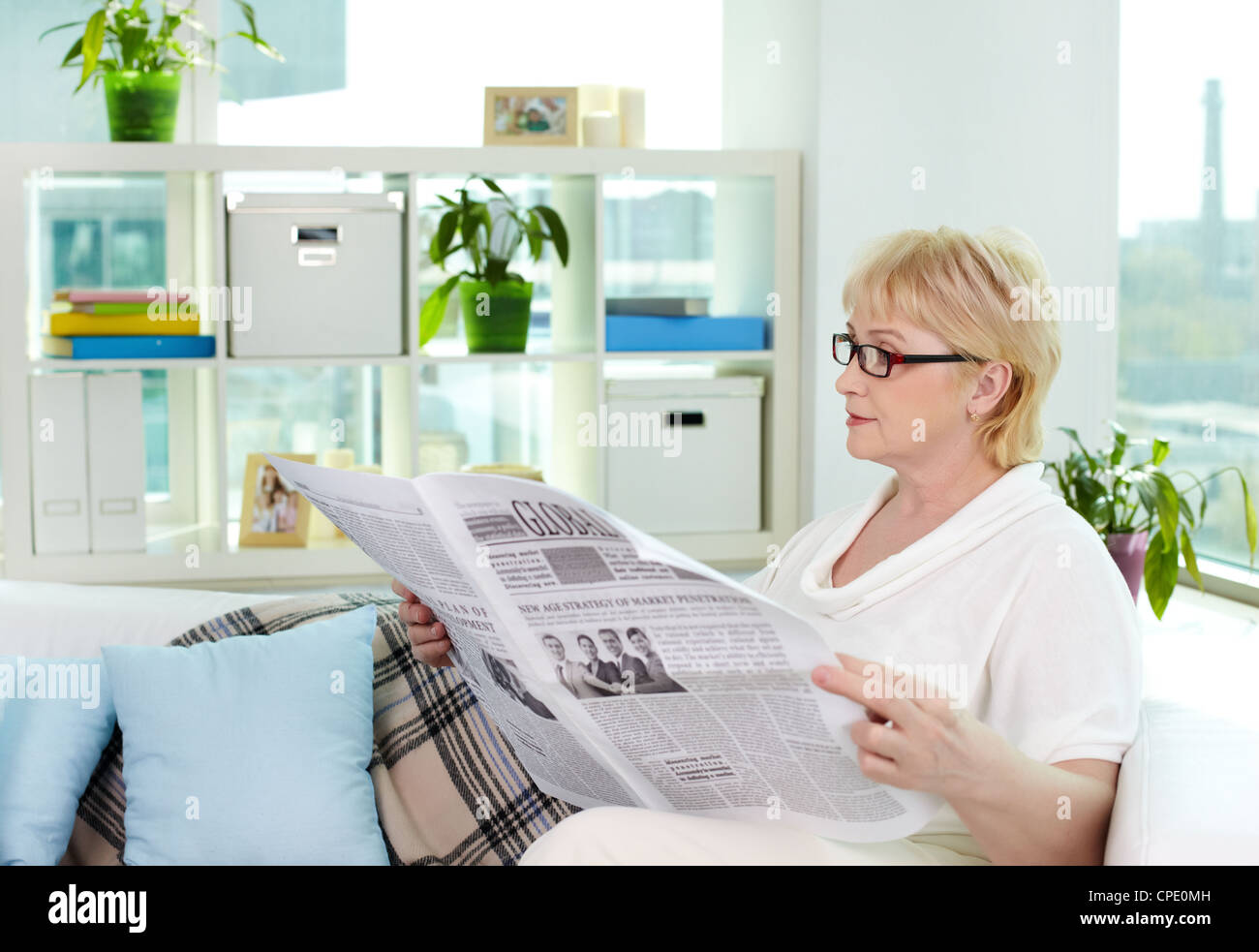 portrait of aged woman reading newspaper at home stock photo