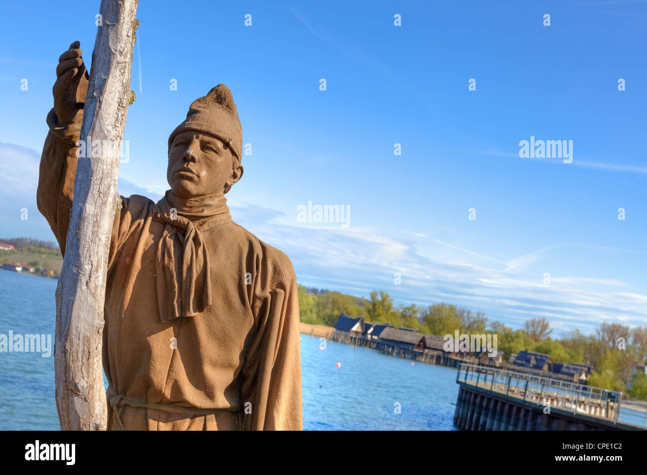 Sculpture of a pile maker in Unteruhldingen pier, stilt houses in the background, Baden-Wurttemberg, Lake Constance, - Stock Image