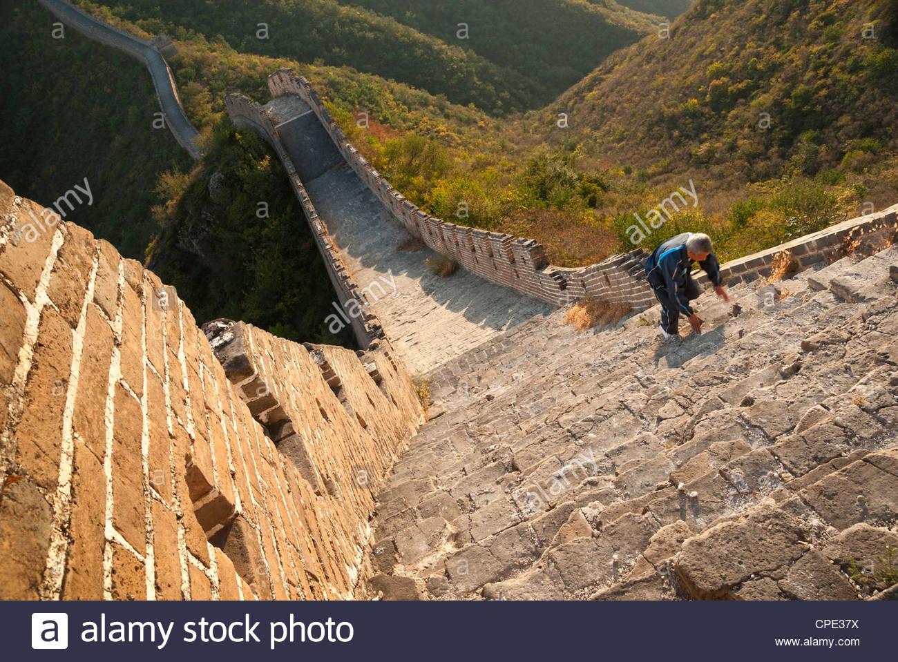 Chinese man climbs Great Wall of China, Huanghuacheng (Yellow Flower) at sunset in autumn, Jiuduhe Zhen, Huairou, - Stock Image