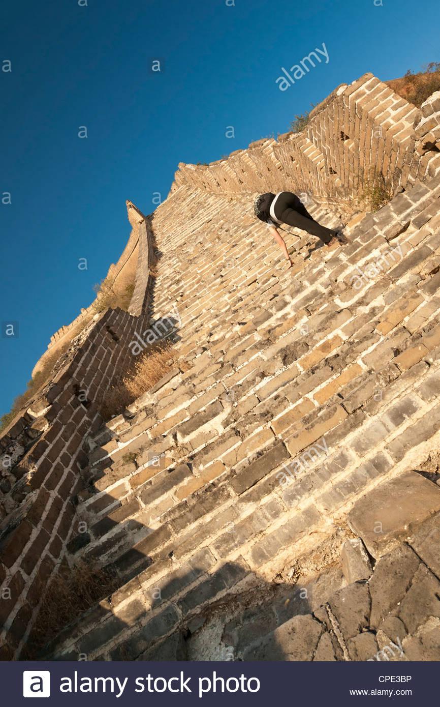 Woman climbing steep steps, Great Wall of China, Huanghuacheng (Yellow Flower), Wild Wall, Jiuduhe Zhen, Huairou, - Stock Image