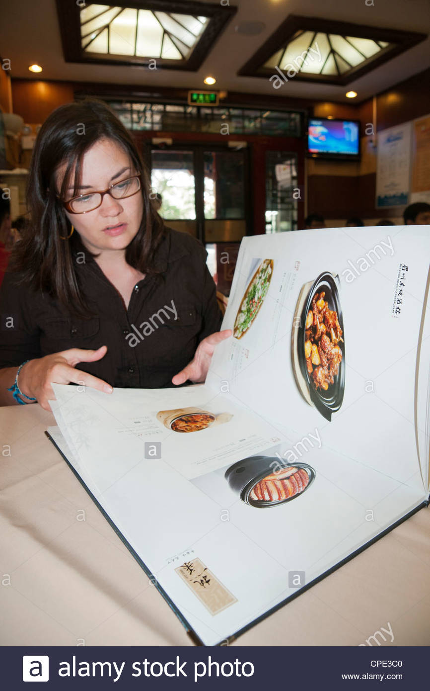Woman with picture menu in Chinese restaurant, Beijing, China, Asia - Stock Image